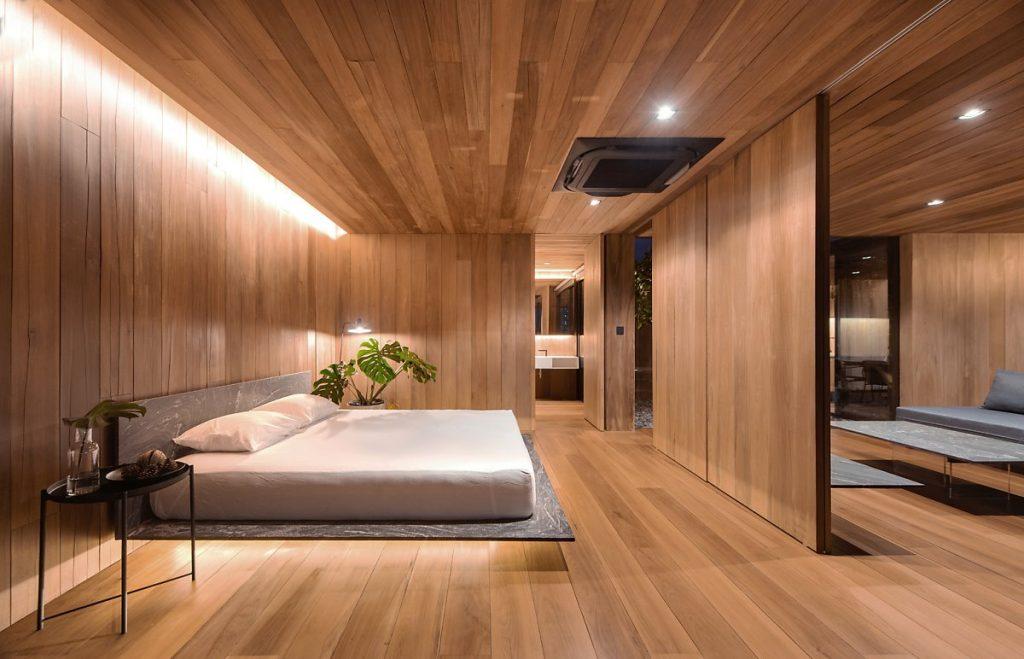 Phòng ngủ ngăn cách với phòng bếp của căn hộ penthouse này qua lớp cửa kéo bằng gỗ lim
