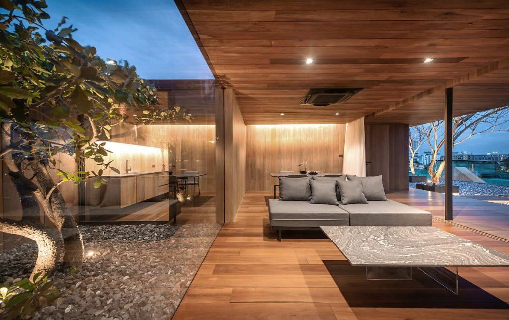 Mảnh sân có nền đá cuội, cùng cây thân gỗ lớn đặt vuông góc với phòng khách