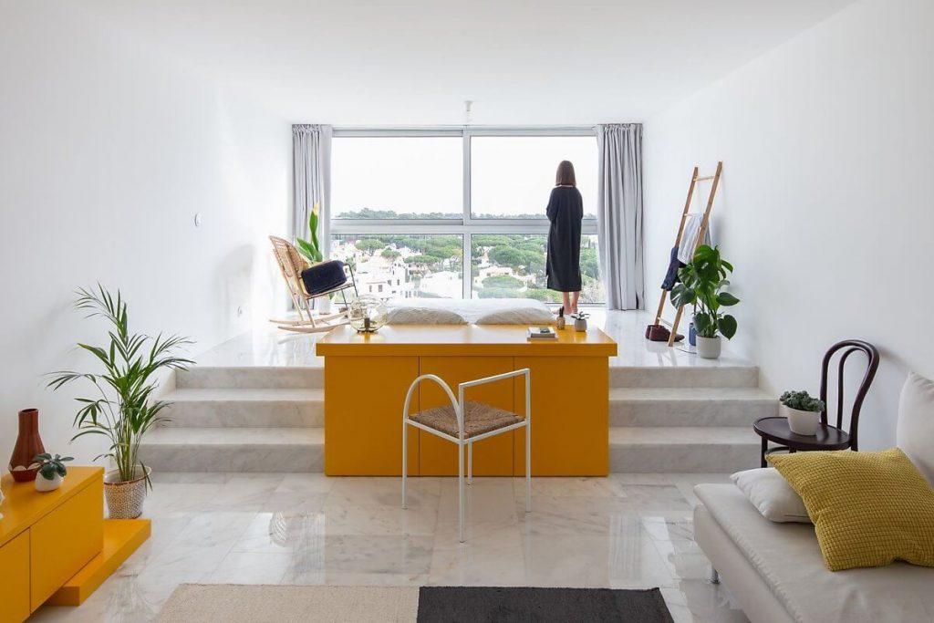 Sàn nhà của căn hộ studio được lát bởi gạch bóng kiếng màu trắng sáng bóng