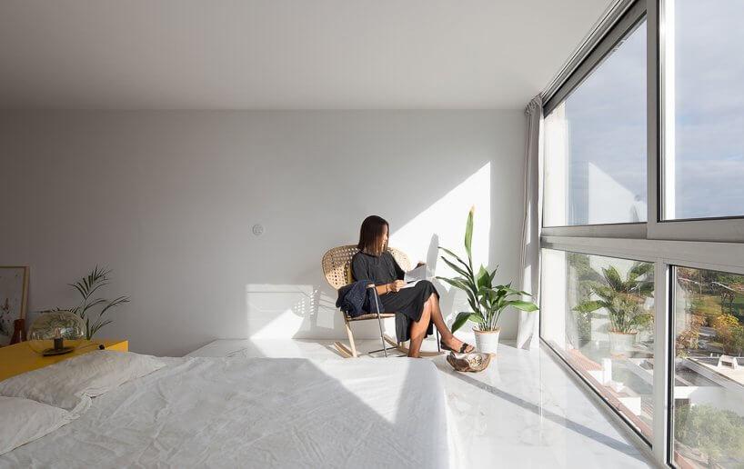 Phòng ngủ của căn hộ studio được đặ ở trên bậc thềm gần cửa sổ