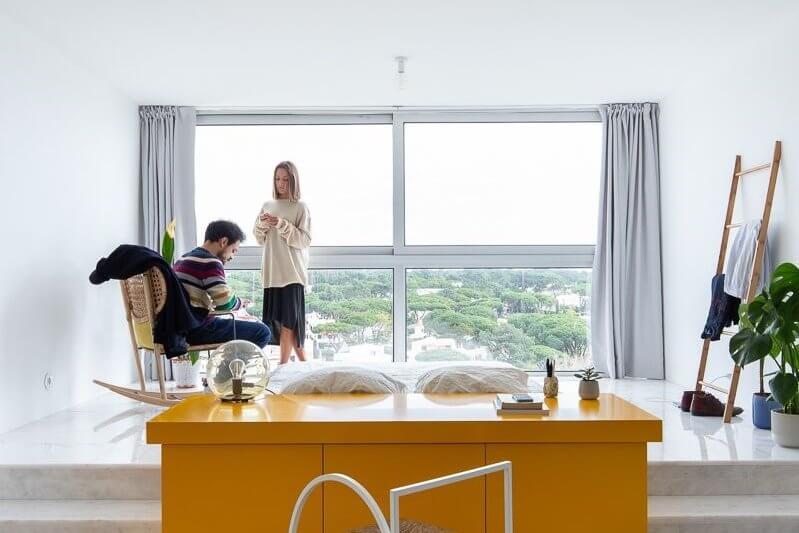 Chiếc kệ tủ màu vàng là vật dụng đa năng để phân chia rõ ràng không gian giữa phòng khách và phòng ngủ