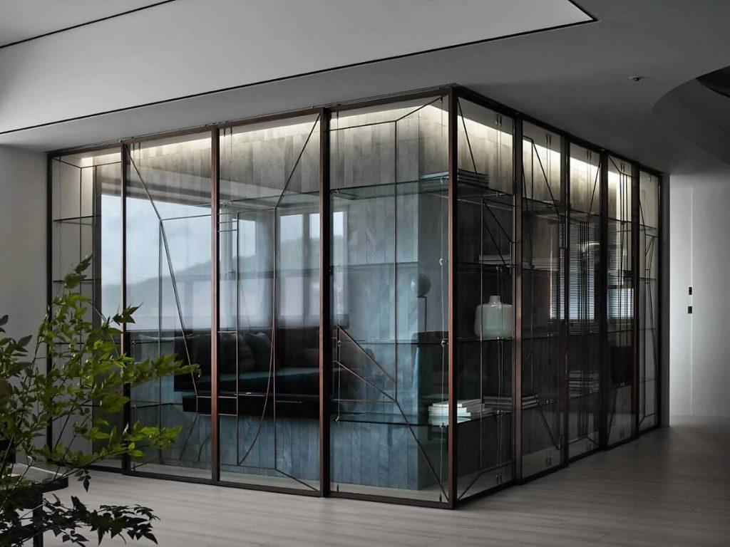 Tủ kính bao quanh khối bê tông để đựng đồ trang trí và TV