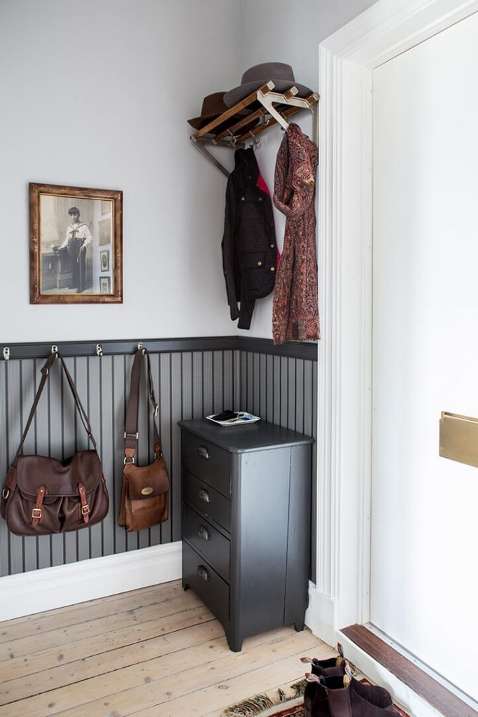 The main hallway in the apartment has a shoe cabinet and wooden floors