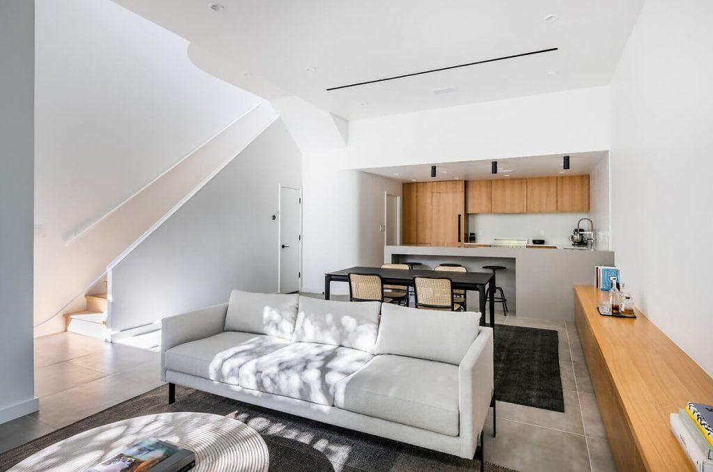 Kệ tủ gỗ công nghiệp từ phòng khách được nối dài ra phòng bếp tạo một tổng thể kiến trúc liên thông