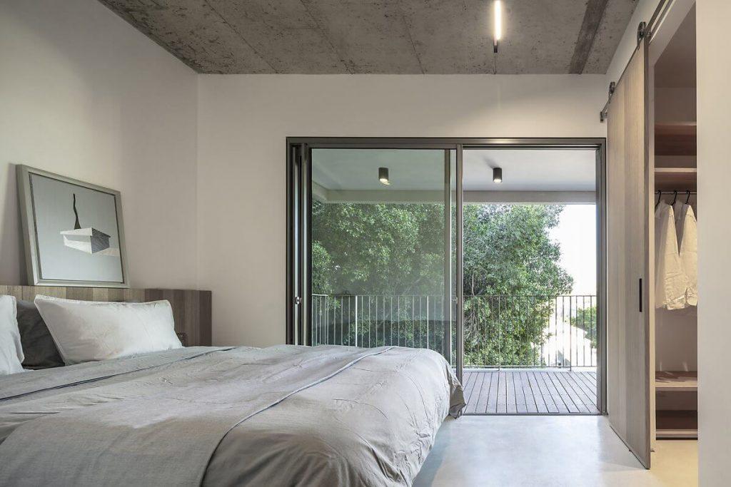 Đặc trưng của xây nhà tiết kiệm chi phí được thể hiện lần nữa tại phòng ngủ qua kiểu trần bê tông