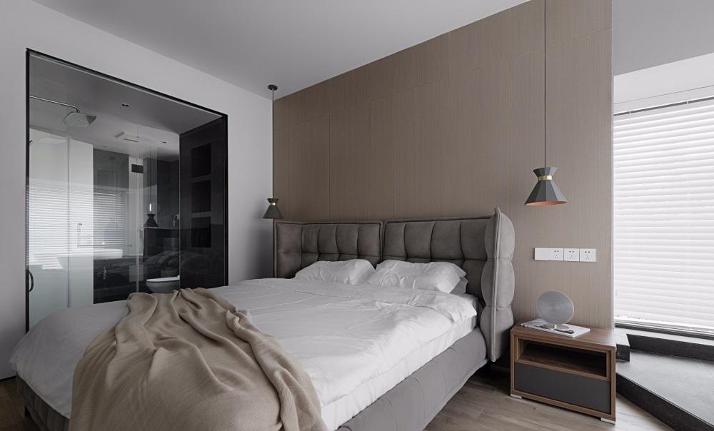giường ngủ lớn với bộ ga đệm màu trắng nâu, đèn ngủ trang trí, kệ tủ, cửa kính trượt ngắn cách phòng ngủ và nhà vệ sinh