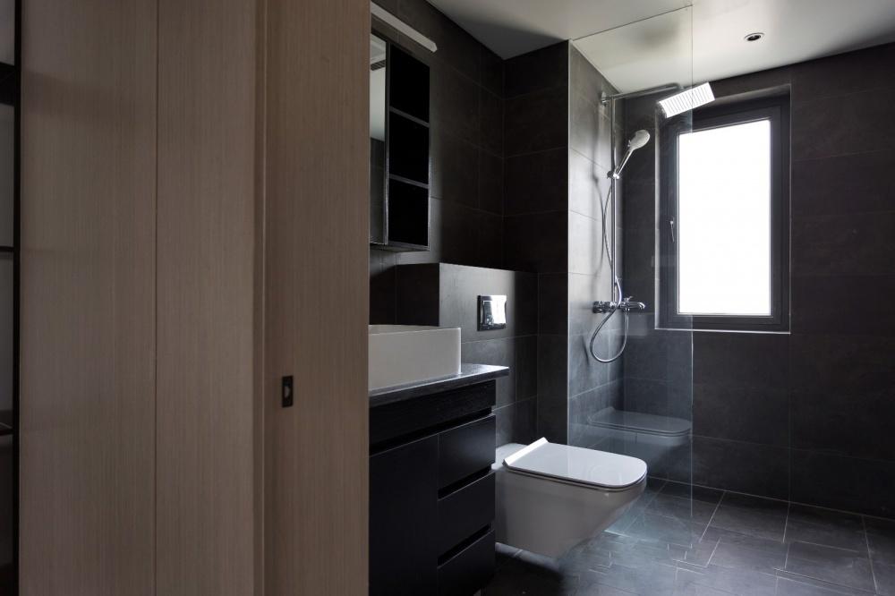 nhà vệ sinh chung sử dụng sàn và tường ốp gạch đen chống trơn trượt, vách tắm kính và vòi sen đứng