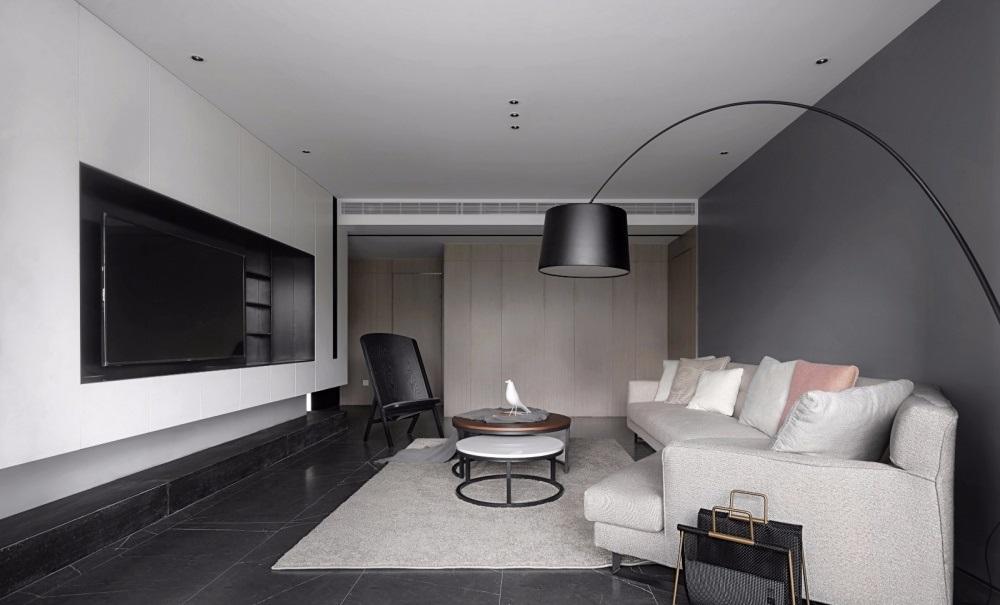 Phòng khách có sofa màu sữa, ghế lười, bàn trà, thảm, sàn gạch đen