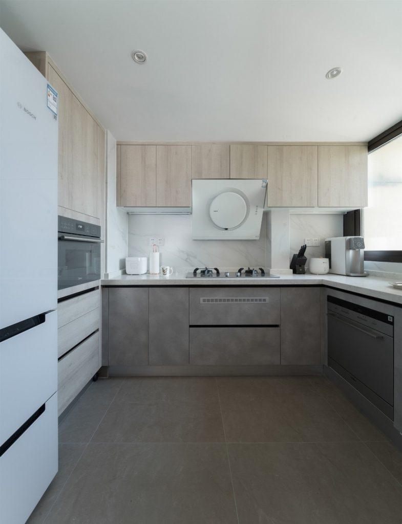 phòng bếp đầy đủ thiết bị nấu nướng, hệ thống tủ gỗ công nghiệp được lắp đặt kịch trần gọn gàng