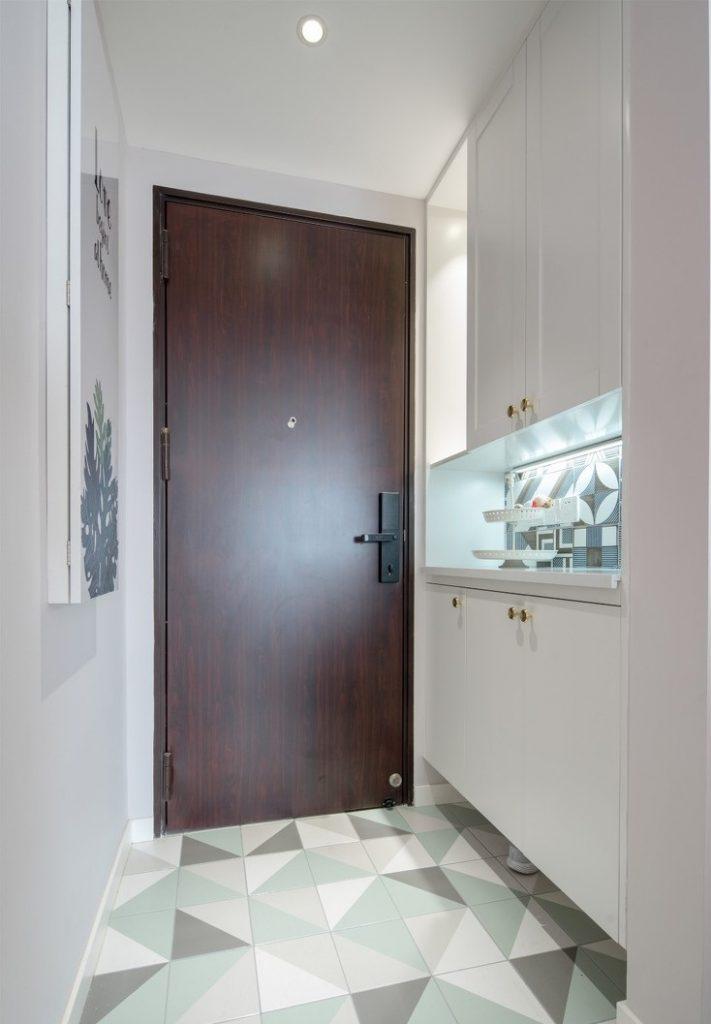 cửa ra vào được thay ổ khóa thông minh bên cạnh là tủ để đồ bằng gỗ