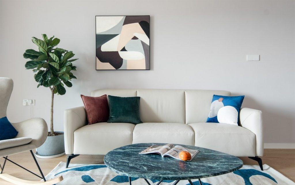 Phòng khách có bộ sofa nhỏ, ghế lười, bàn trà xanh ngọc vân đá, đồ trang trí decor