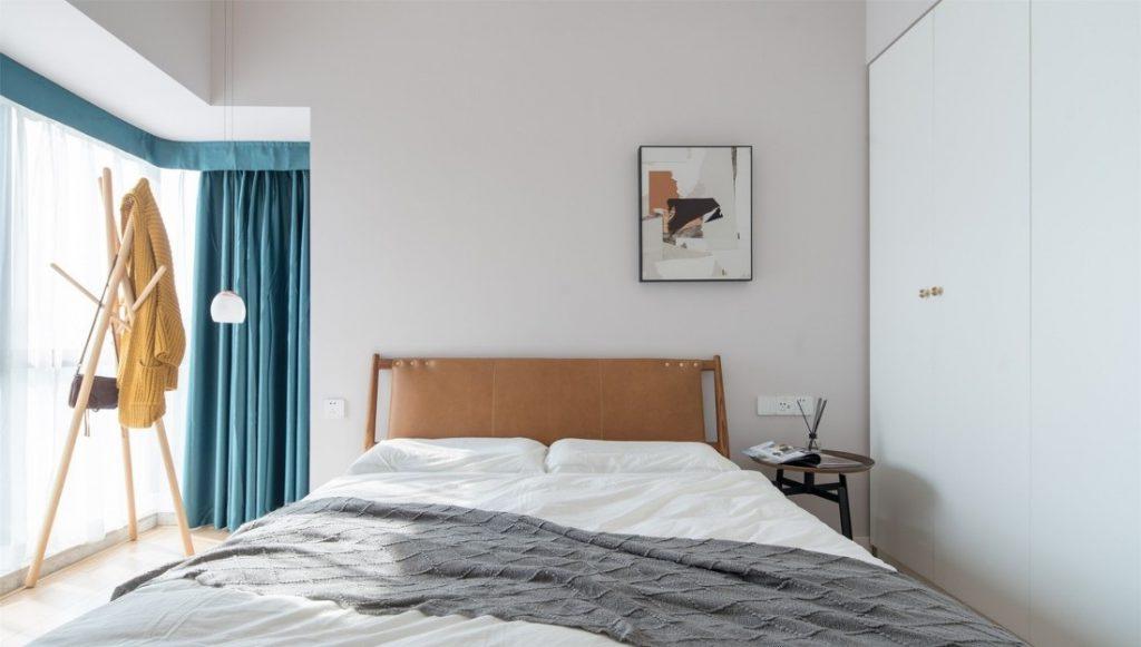 Bên cạnh giường ngủ là tủ gỗ màu trắng bóng dễ lau chùi và không gian lưu trữ quần áo lớn - cải tạo chung cư cũ