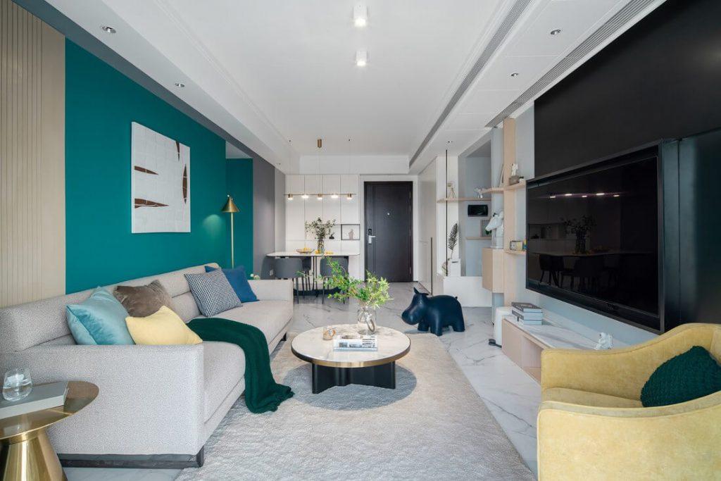 Phòng khách có bộ ghế sofa, thảm lót lông màu xám, bàn trà nhỏ tranh tráng trí