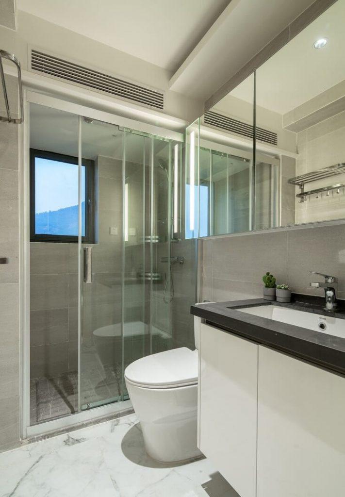Nhà vệ sinh sử dụng tông màu trắng đầy đủ các thiết bị vệ sinh và tủ gương cảm ứng cùng vách ngăn kính tiện nghi