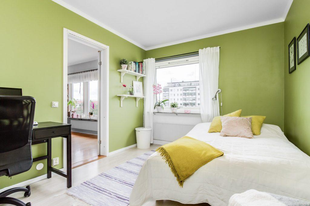Phòng ngủ dùng tông màu xanh lá và giường ngủ có ga màu trắng