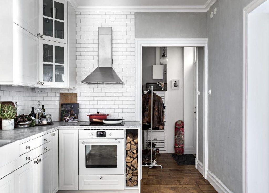 Gian bếp với tông màu trắng chủ đạo có máy hút mùi và lò nướng hiện đại - thiết kế căn hộ nhỏ