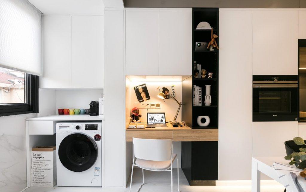 bàn làm việc và kệ tủ trưng bày màu đen, bên cạnh là máy giặt và cốc nước trang trí