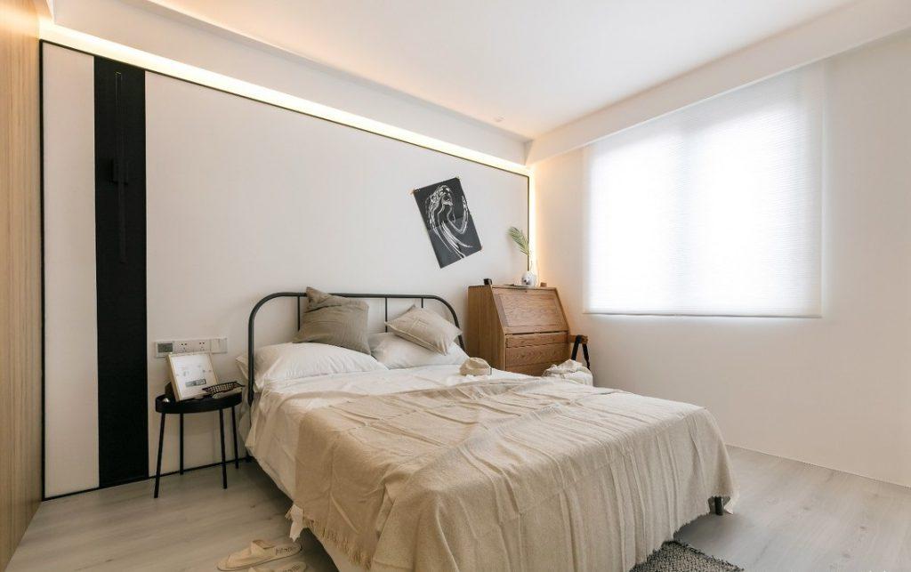 giường ngủ lớn cùng bộ ga đệm sáng màu. phía sau là tấm nhựa pvc cùng dải đèn led trang trí