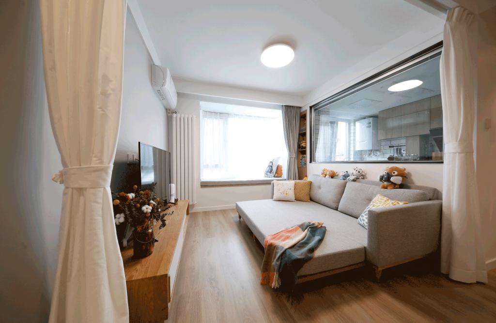 phòng khách có đặt một bộ sofa màu xám có thể linh hoạt biến thành giường ngủ