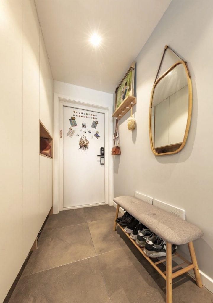 Hành lang chính ra vào căn hộ được đặt một tủ gỗ công nghiệp trắng, kệ để giày, gương
