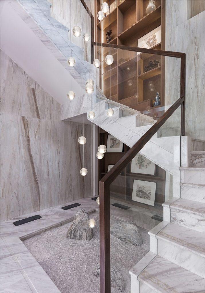 lan can cầu thang bằng kính và nền được ốp bằng đá cẩm thạch, đèn trang trí cầu thang