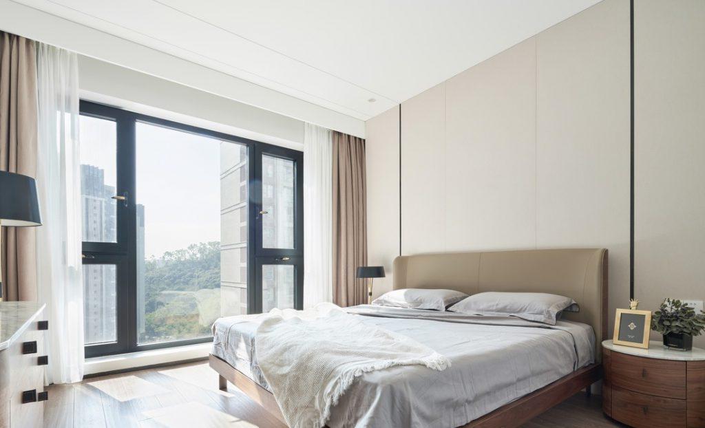 Das Schlafzimmer hat ein großes Bett, große Fenster, Gipskartondecken und Holzböden