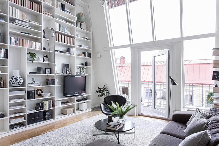 ห้องนั่งเล่นพร้อมชั้นเก็บของและประตูกระจกขนาดใหญ่ที่สวยงาม - การออกแบบอพาร์ทเมนท์ดูเพล็กซ์