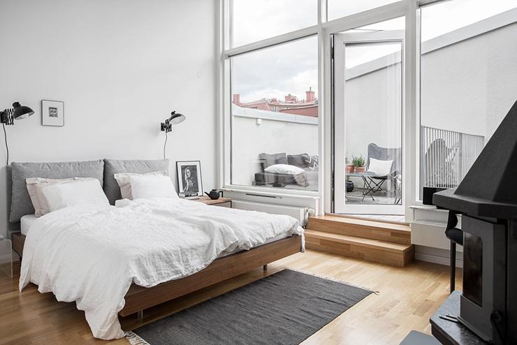 ห้องนอนใหญ่มีที่นอนสีขาวและสีเทาและประตูกระจกขนาดใหญ่ - แบบดูเพล็กซ์อพาร์ตเมนต์