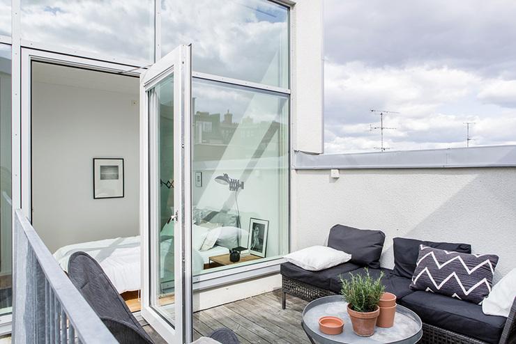 ระเบียงบนชั้น 2 มีชุดโซฟาสีเทาที่สวยงามและพื้นไม้เชิงนิเวศ - อพาร์ทเมนท์ 2 ชั้น
