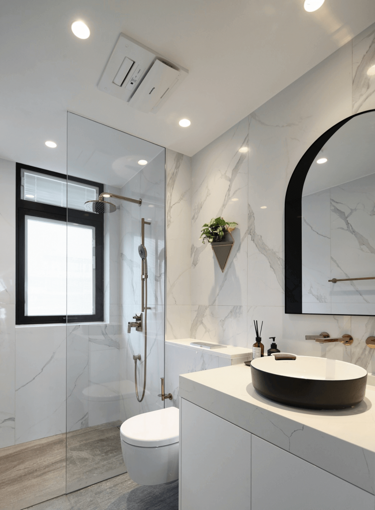 The shared bathroom of the penhouse apartment has a washbasin with cabinet design right below, a mirror and a glass shower enclosure