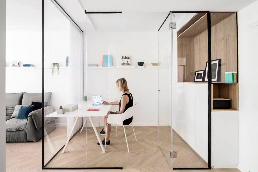 قسم زجاج مقسّم يقسم غرفة العمل مع مساحة معيشة مشتركة