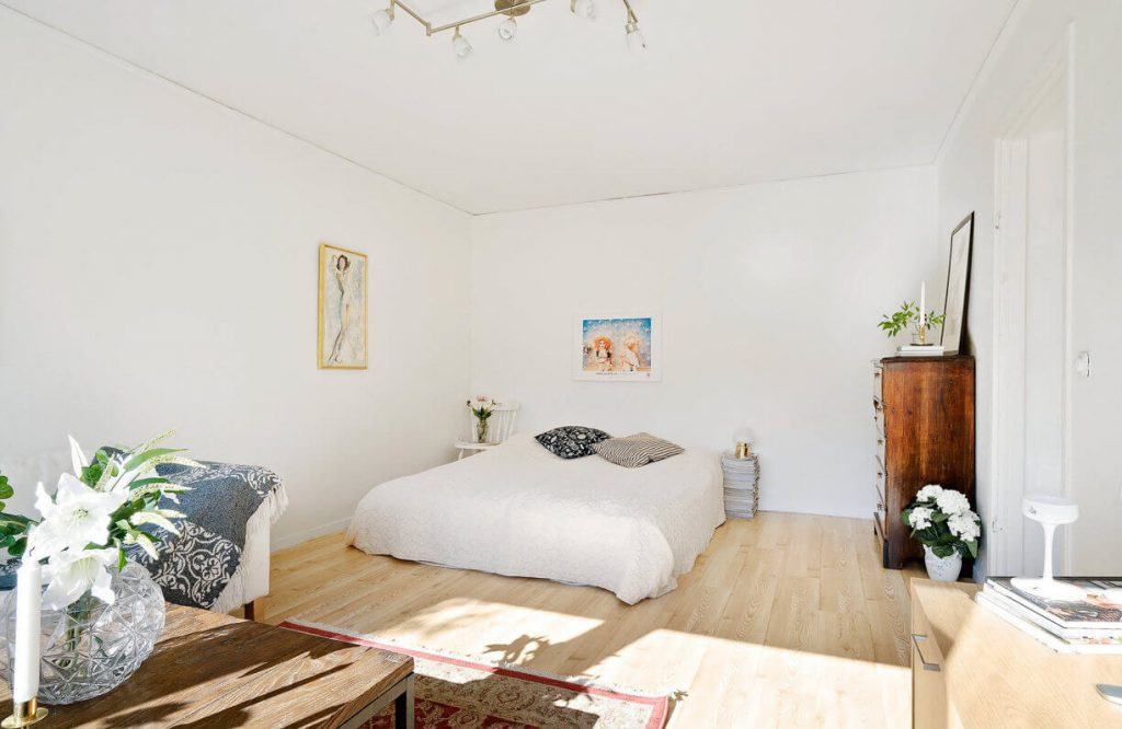 The bed area has large white cushions and beautiful wall paintings - 1-bedroom apartment