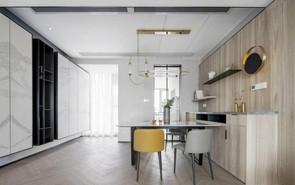 La salle à manger a une table à manger compacte, des armoires en bois industrielles le long de la salle à manger