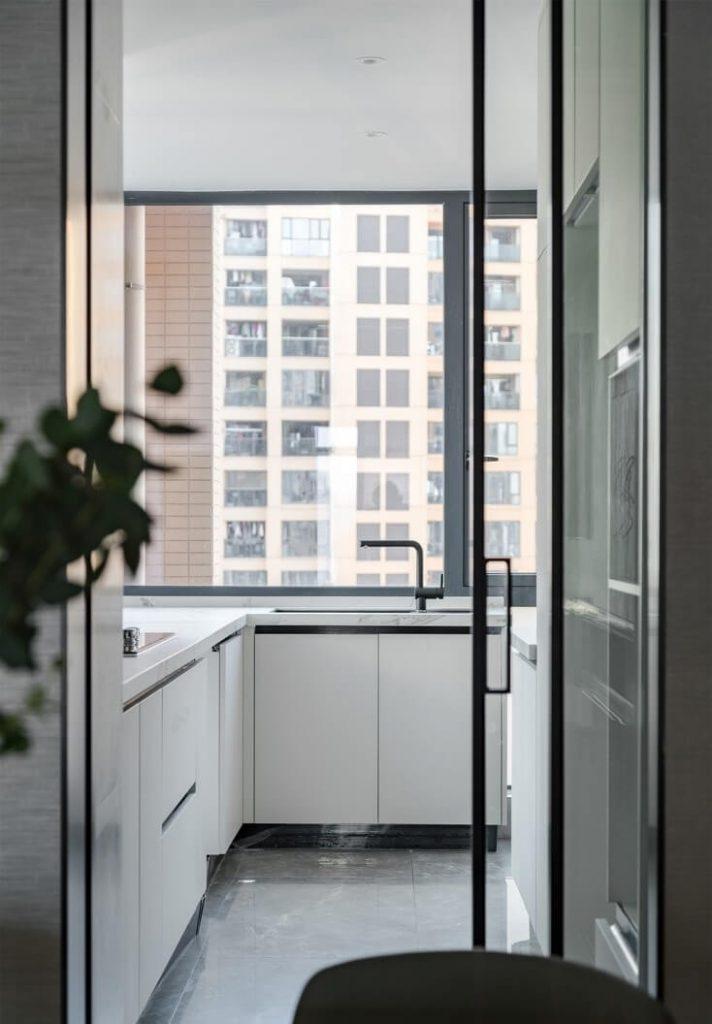 Cuisine entièrement équipée avec équipement de cuisine de base et grandes fenêtres de ventilation.