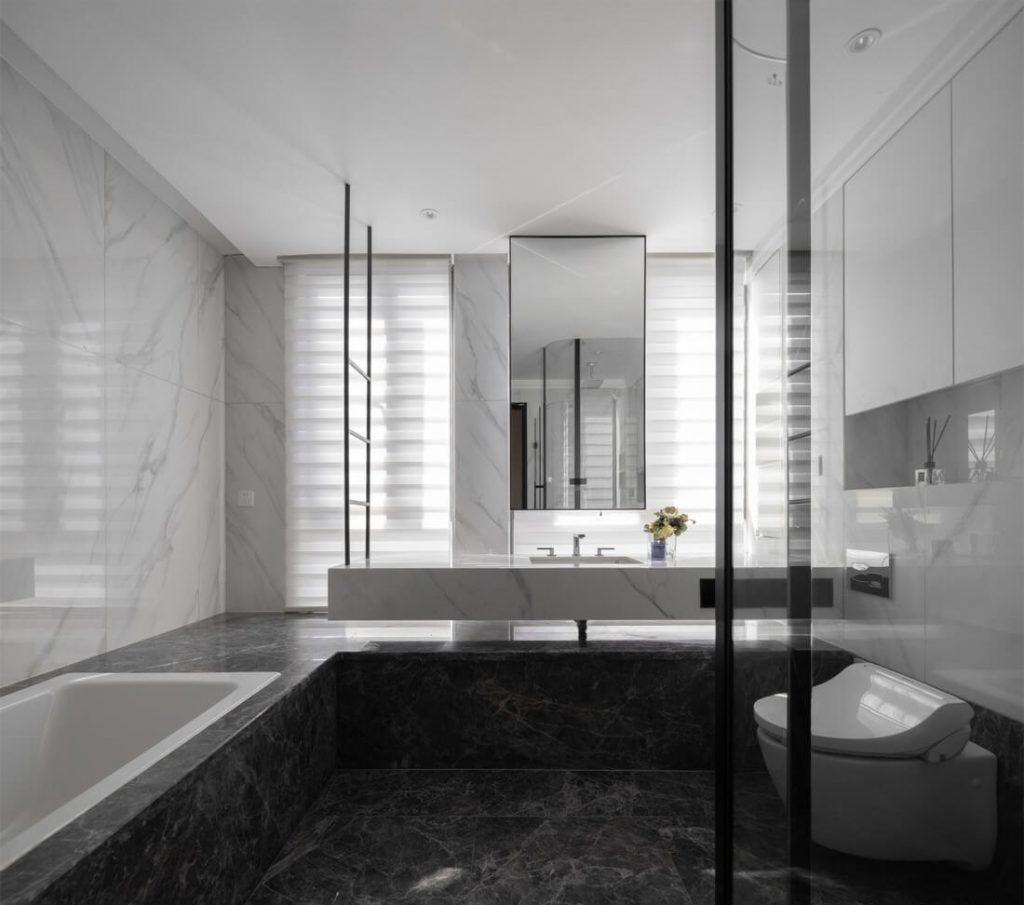 バスルームは黒いセラミックタイルと浴槽、モダンなガラス張りのシャワーウォールを使用