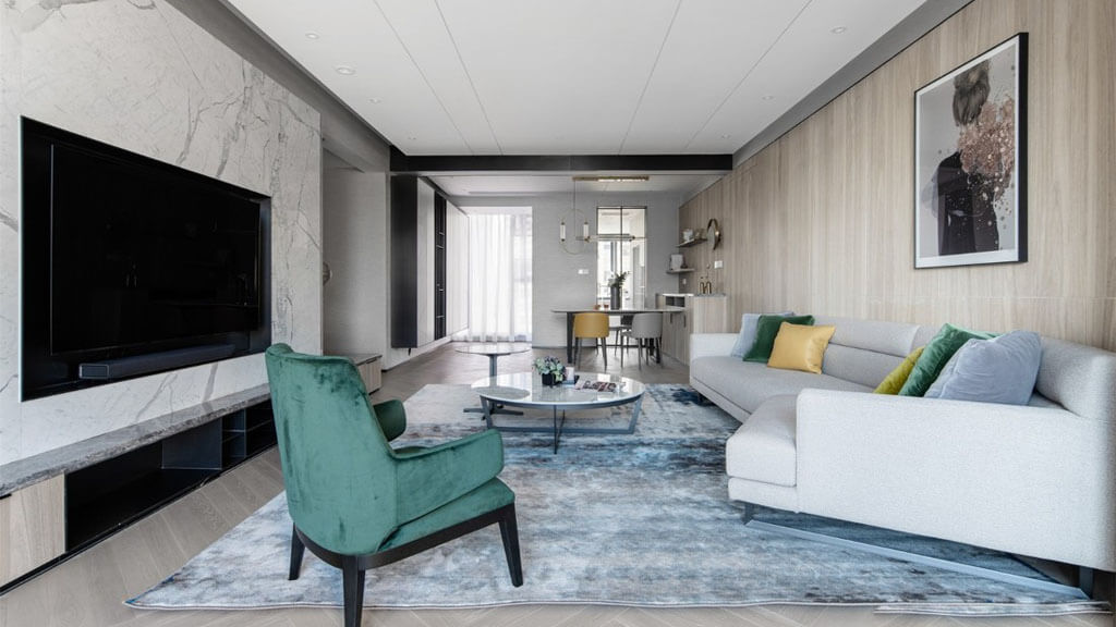 リビングルームにはティーテーブルとゆったりとした椅子が置かれた広々としたソファーセットがあり、下は冷たい色のラグです。