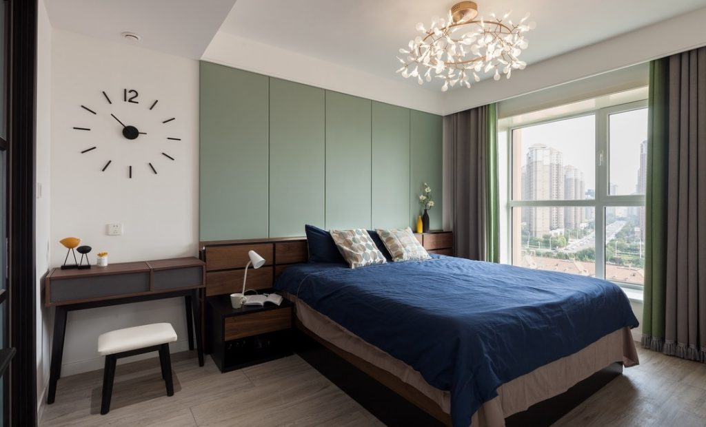 The main bedroom has a large bed in the middle, next to a small desk, a large decorative clock face.