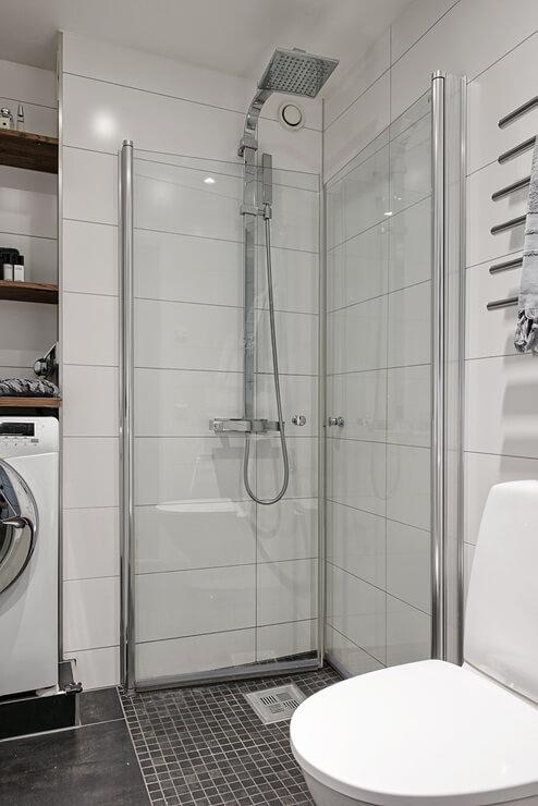 Nhà vệ sinh có nền gạch đen, vòi tắm đứng và vách ngăn kính