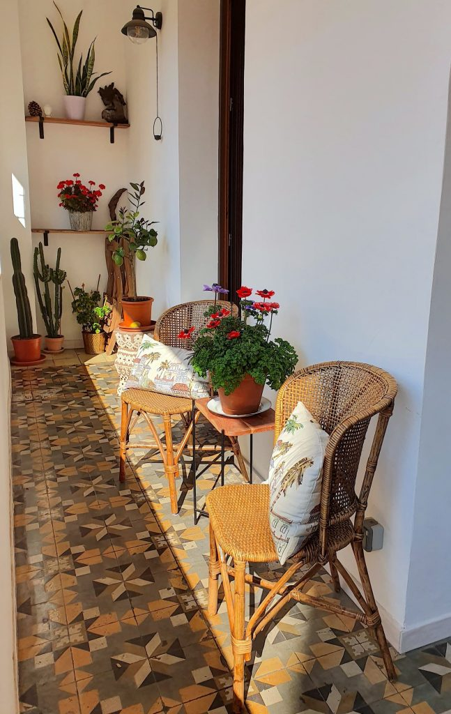 The balcony has a small table and chairs and an old floral tile background