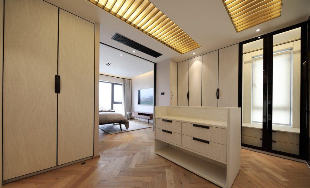 Phòng thay đồ với nhiều tủ gỗ công nghiệp kê kịch trần, sử dụng cửa kính và cửa tủ gỗ