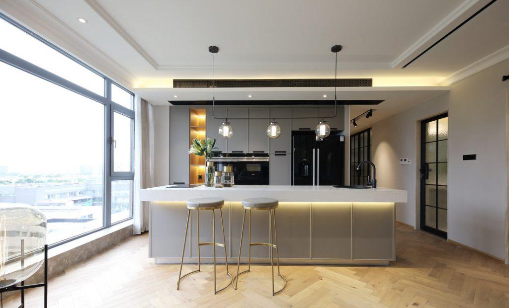 Quầy bar bếp được làm bằng đá nhân tạo, có ghế chờ cao và áng sáng led vàng trang trí ấm cúng - nội thất bắc âu