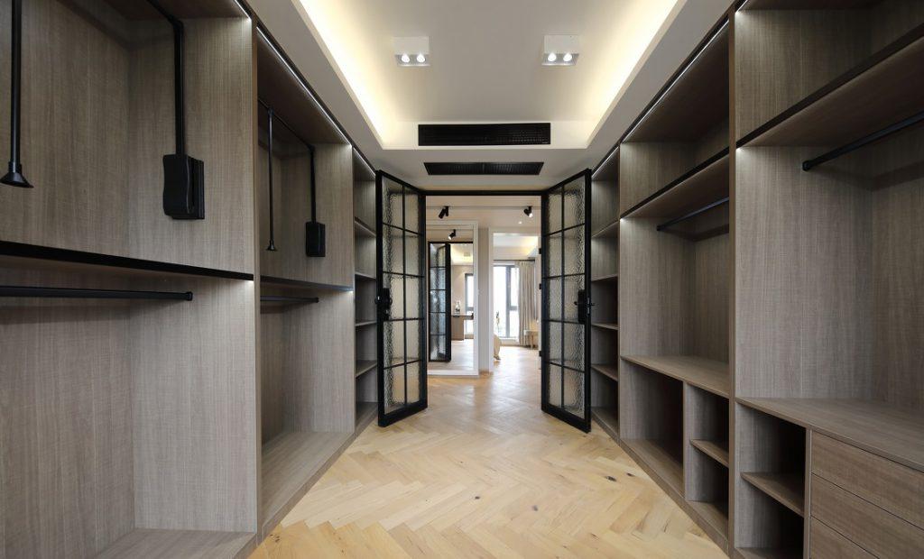 Phòng làm việc có kệ để đồ bằng gỗ sơn màu nâu chạy dọc hai bên tường đem lại không gian lưu trữ lớn