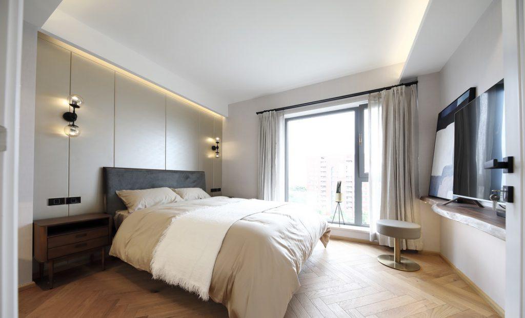 Phòng ngủ phụ có giường lớn cùng bộ ga đệm và rèm cửa màu trắng sữa, đầu giường là tấm PVC bọc da và đèn ngủ sang trọng