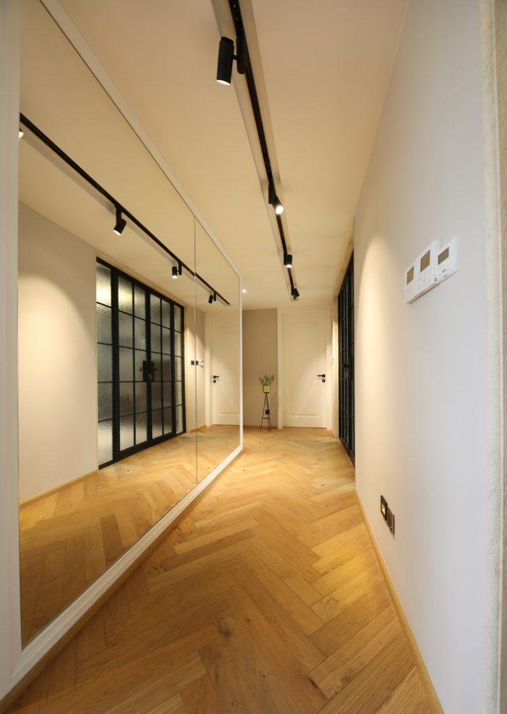 Lối đi hành lang được thiết kế với một bức tường gương, cùng đèn trần nghệ thuật, sàn ốp gỗ hình xương cá - nội thất bắc âu