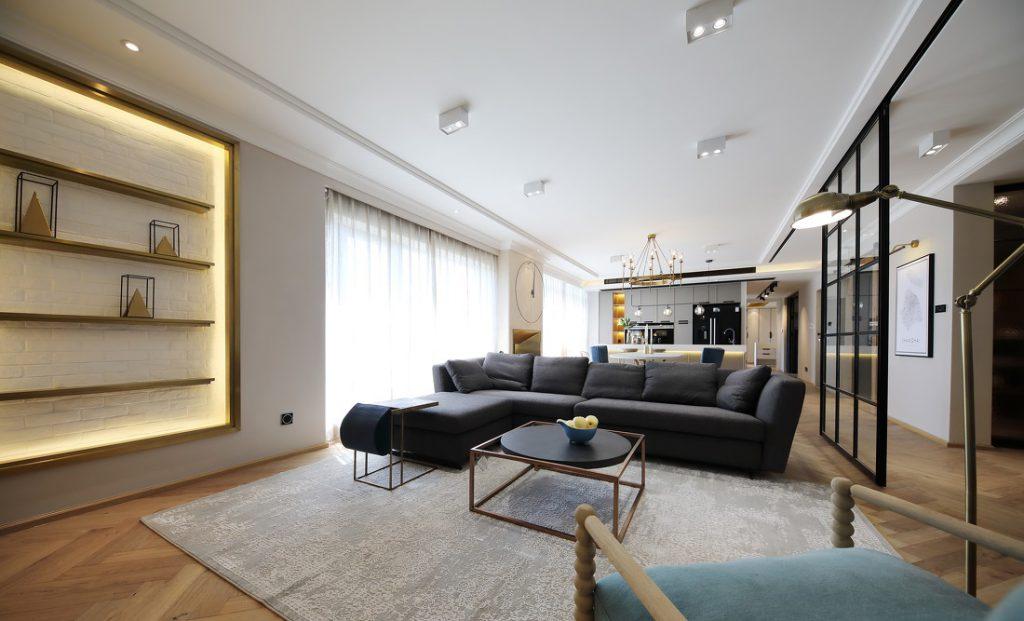 Phòng khách có bộ sofa lớn màu xám, bàn trà, thảm lót, kệ để đồ trang trí có gắn đèn led chìm
