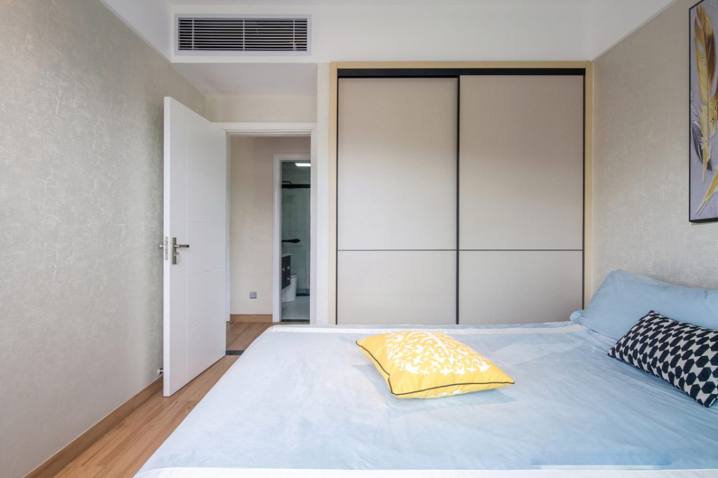 The main bedroom has a large double bed, which uses a peaceful blue mattress, a wardrobe with sliding doors