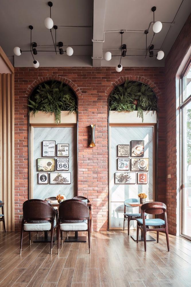 装饰砖墙和绘画,经典桌子和椅子,并在天花板上装上装饰灯-不错的咖啡馆