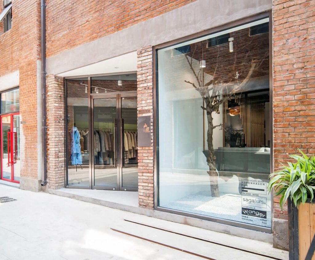 The entrance hall is designed with large glass doors placed slightly diagonally to create a highlight on the brick wall - clothing shop design